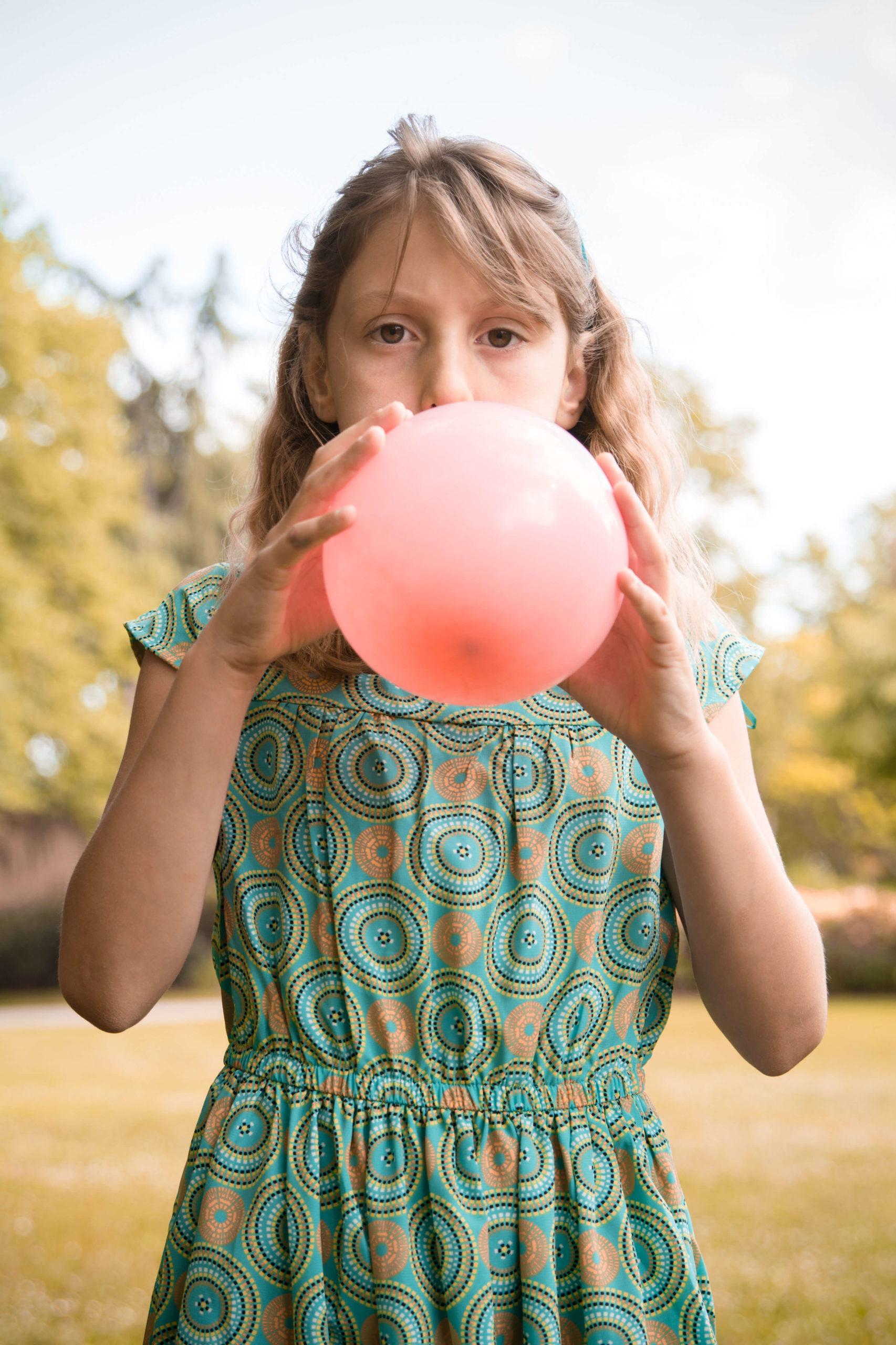 Portrait d'une petite fille soufflant dans un ballon.