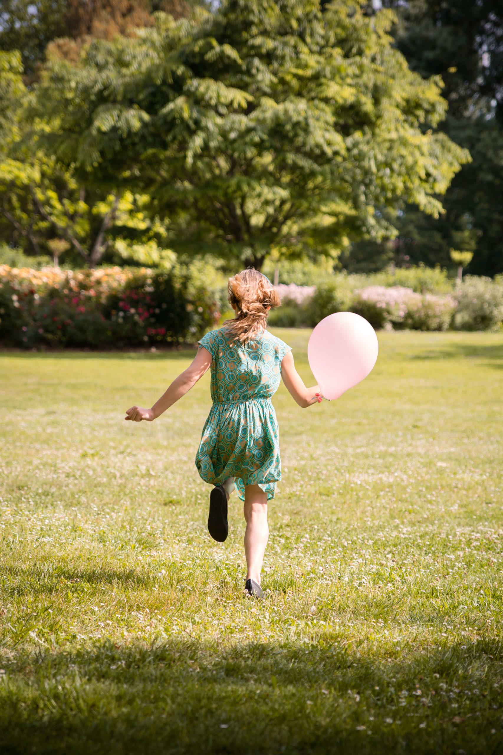 Photographie d'une petite fille de dos, s'éloignant en courant, tenant un ballon gonflable.