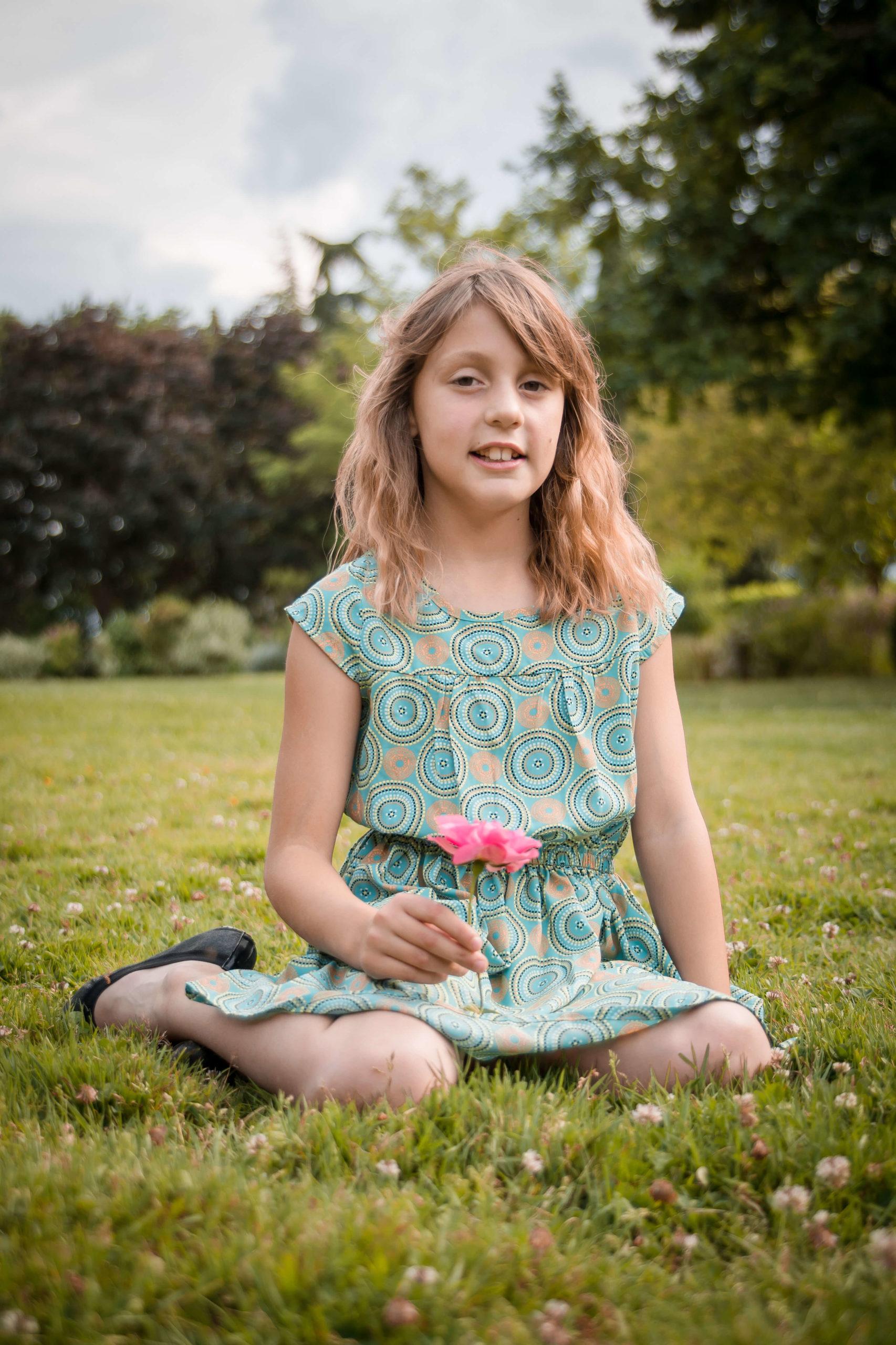 Portrait d'une petite fille assise dans l'herbe et tenant une fleur.