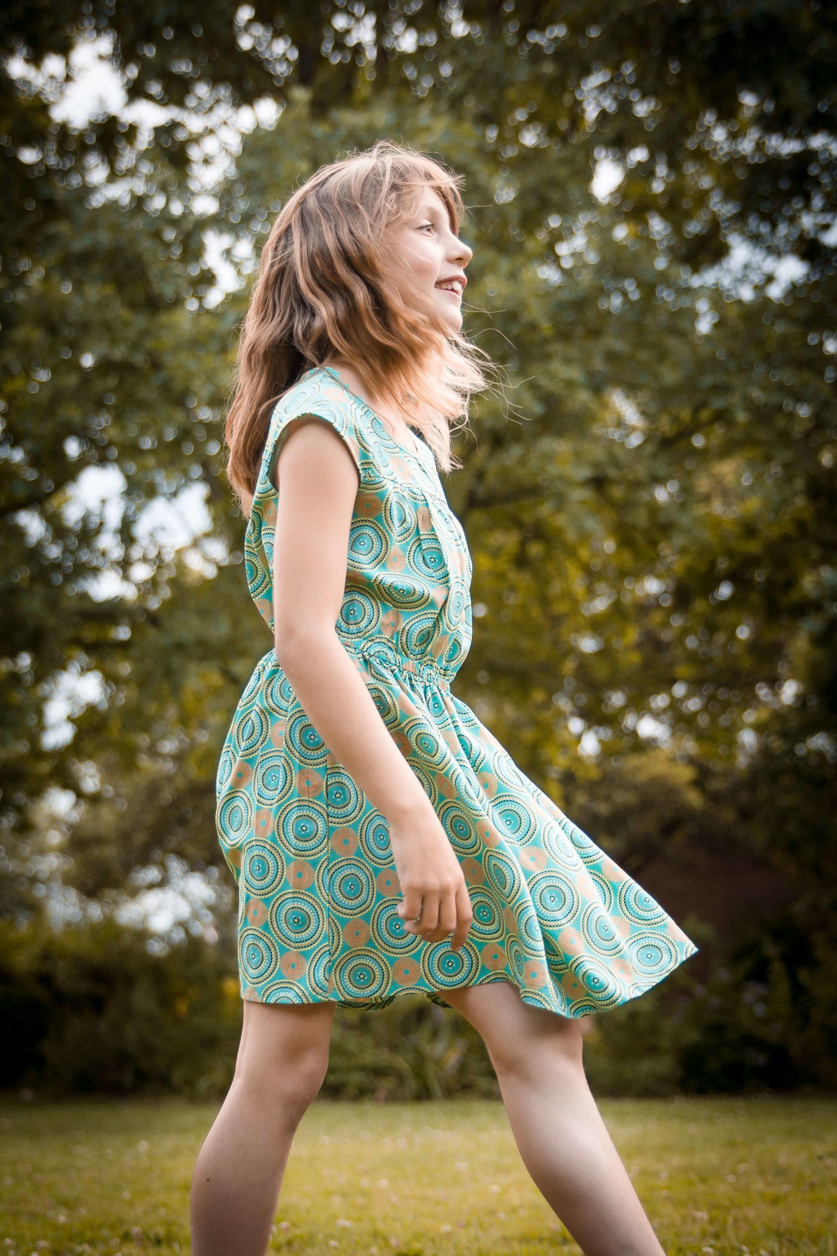 Photographie d'une petite fille jouant dans un parc, la robe et les cheveux au vent.