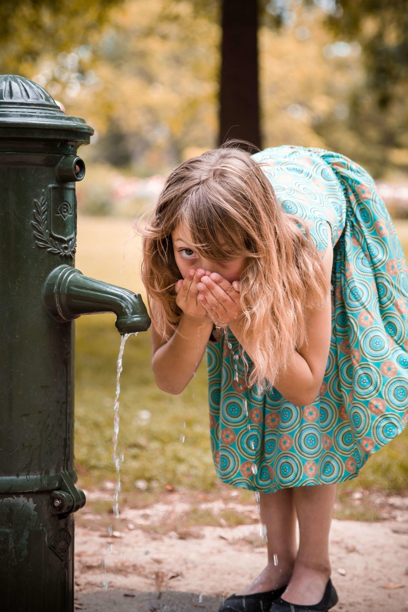 Photographie d'une petite fille buvant l'eau d'une fontaine.
