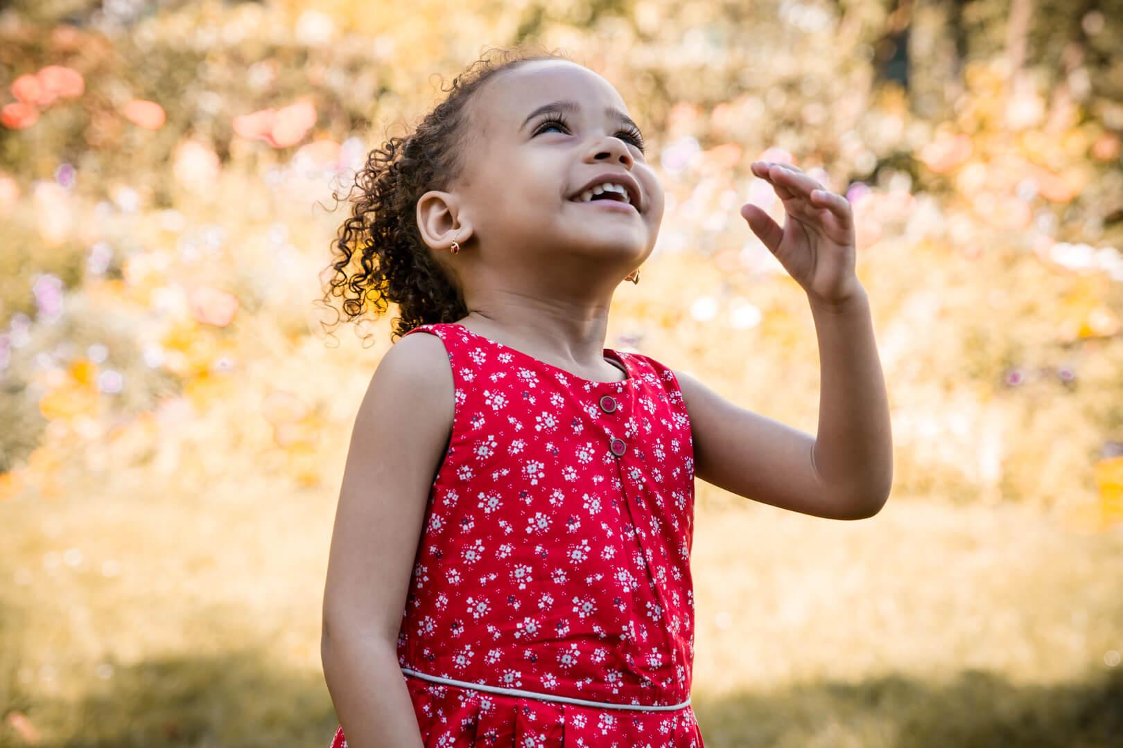 Portrait d'une petite fille en robe rouge riant aux éclats