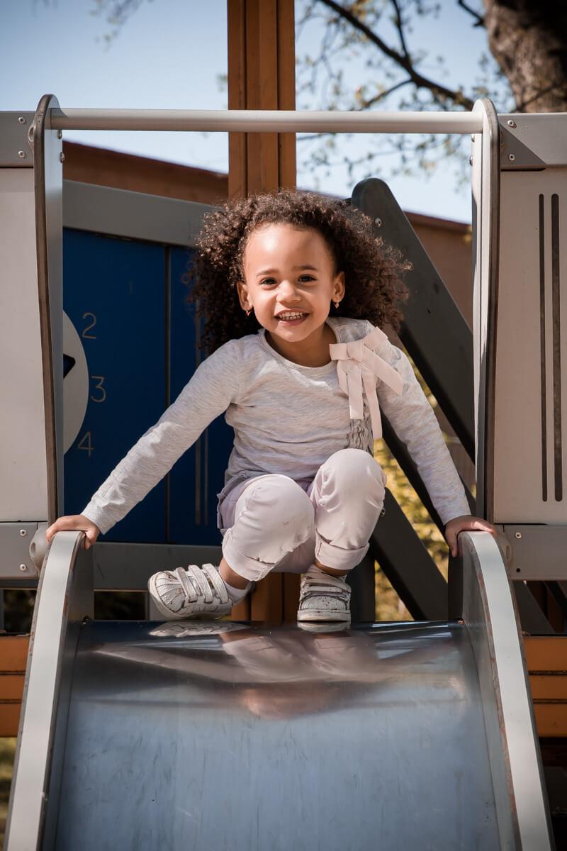 Portrait d'une petite fille descendant un toboggan