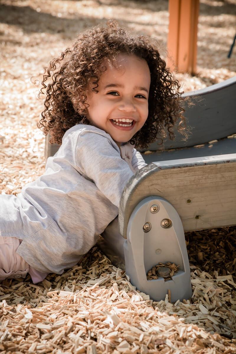 Portrait d'une petite fille souriante au pied d'un toboggan