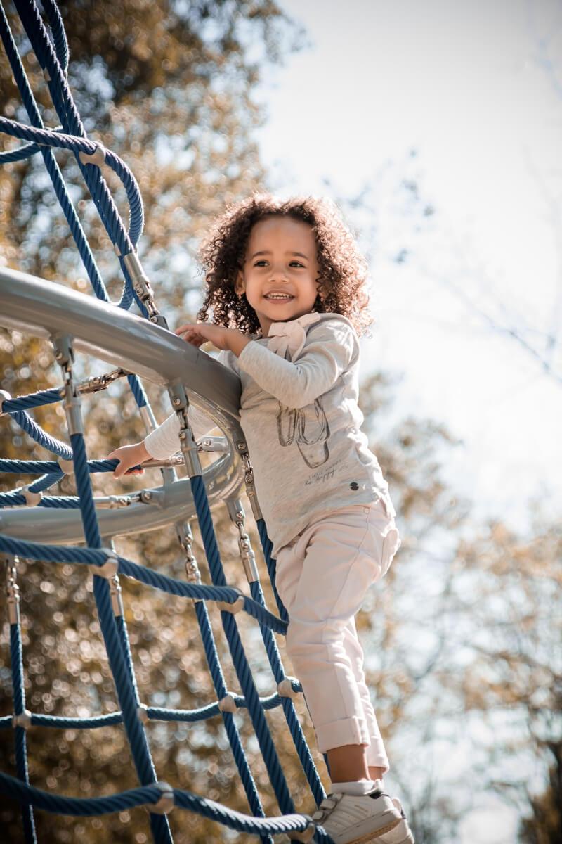 Portrait d'une petite fille escaladant une structure sur une aire de jeux pour enfants