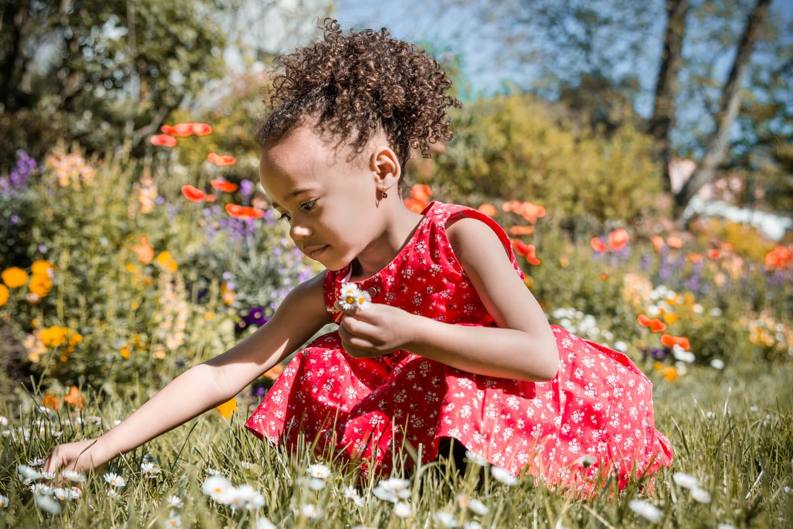 Portrait d'une petite fille en robe roge qui cueille des fleurs