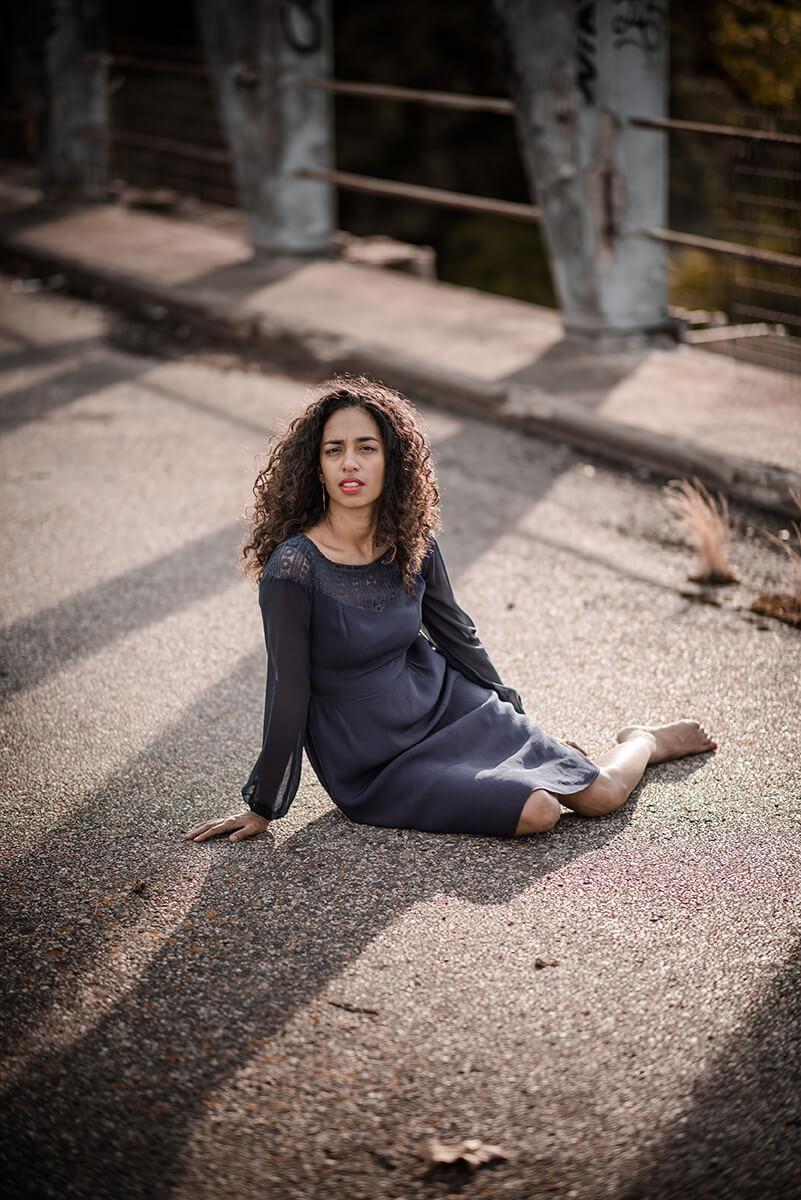 Portrait d'une jeune femme en robe bleue assise sur le sol, sur un pont désaffecté à Toulouse, dans la lumière du soleil couchant.