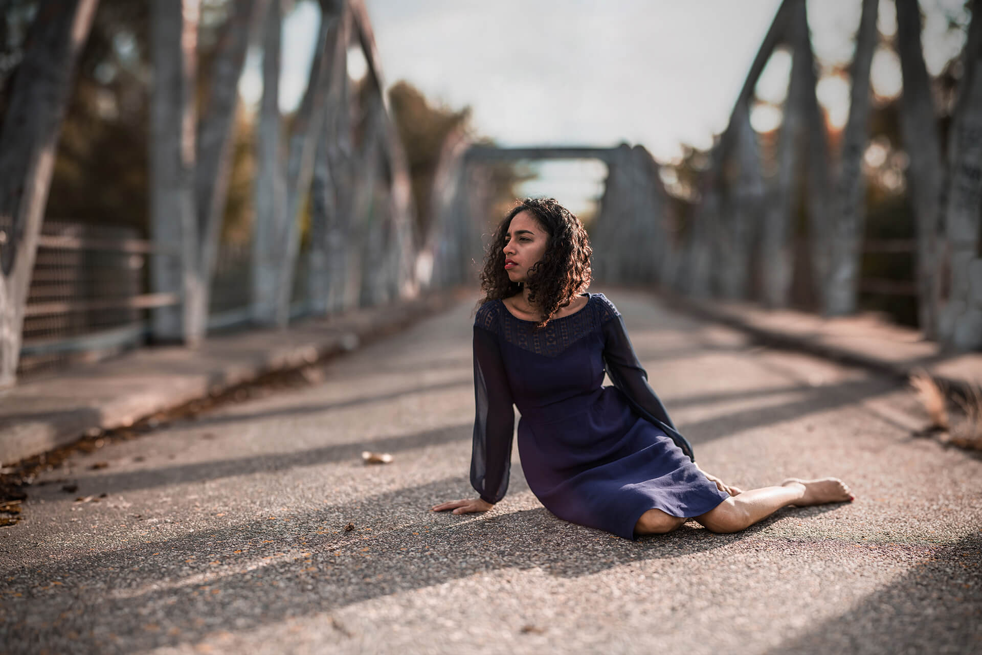 Portrait d'une jeune femme assise sur le sol, sur un pont désaffecté à Toulouse. La photographie a été prise à l'aide de la méthode