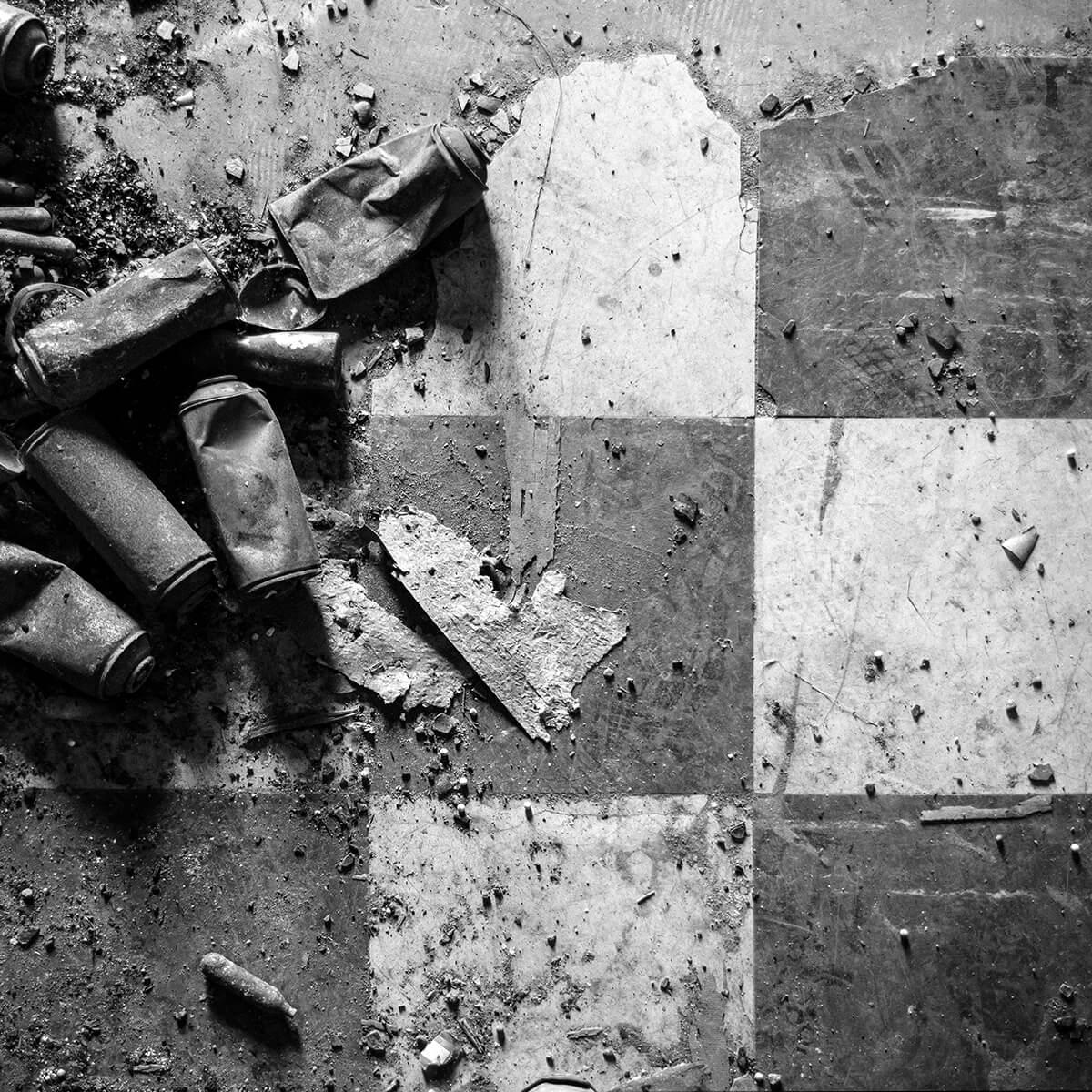 Photographie en noir et blanc du détail du sol d'un bâtiment désaffecté à Toulouse. Un carrelage en damier est jonché de bombes de peinture usagées.
