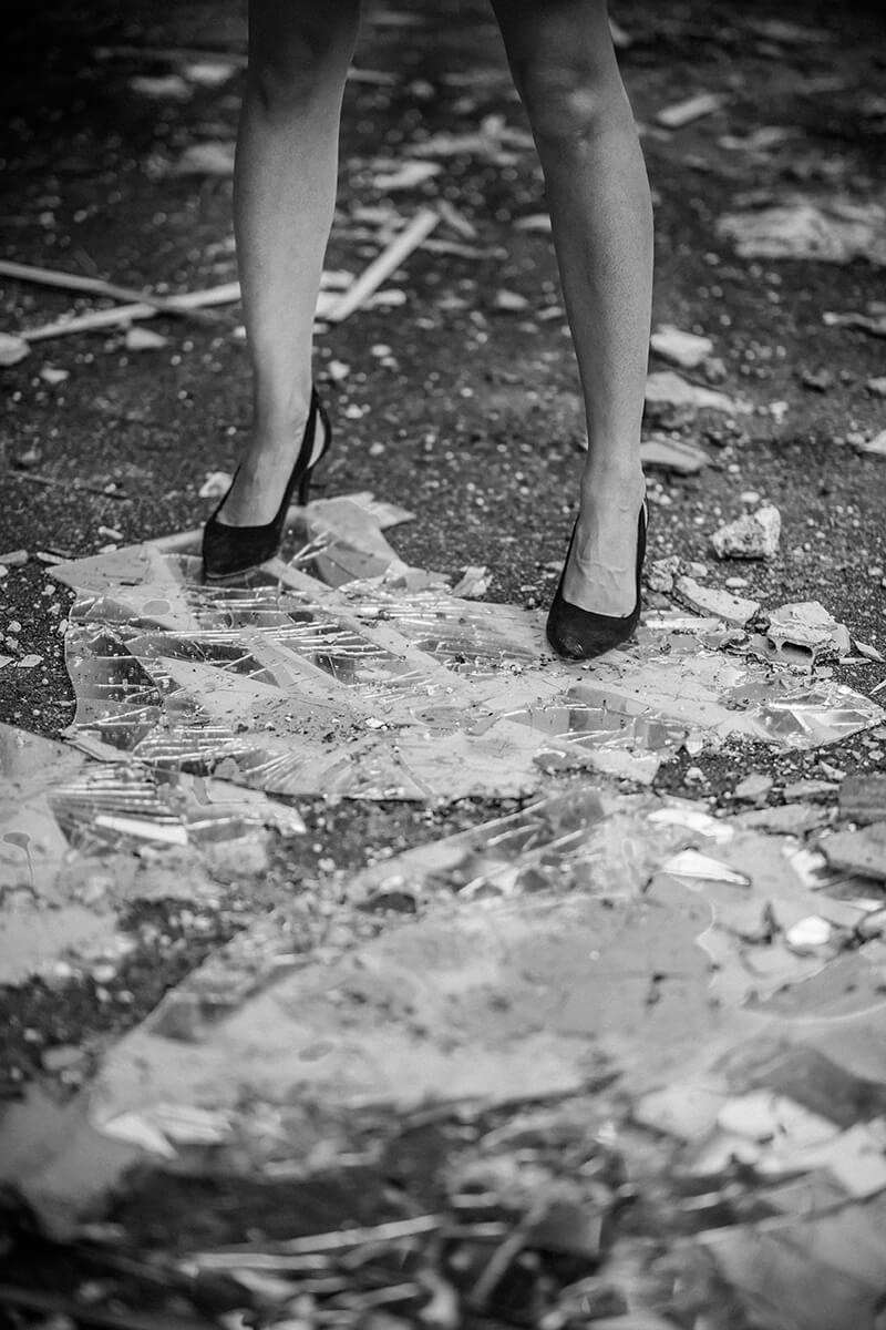 Une photographie en noir et blanc des jambes d'une jeune femme se tenant debout, en chaussures à talons aiguilles, sur des débris de verre.