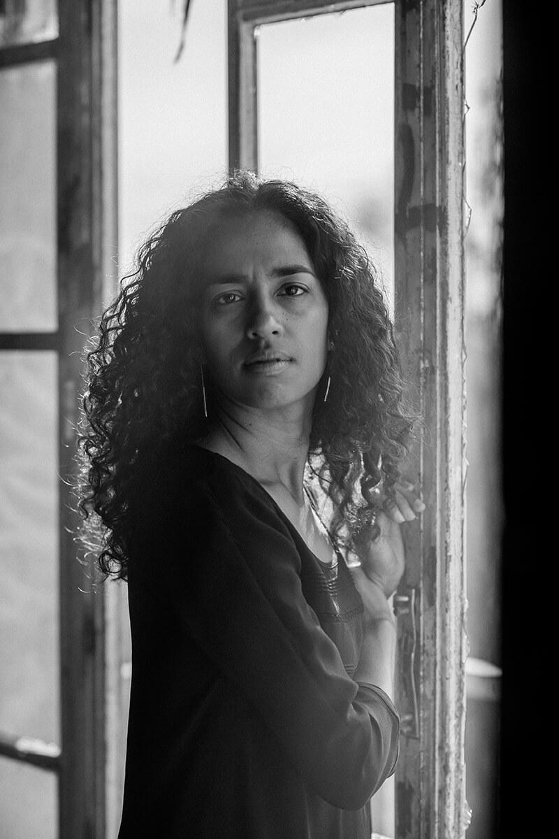 Un portrait en noir et blanc d'une jeune femme se tenant devant une fenêtre, dans un bâtiment abandonné.