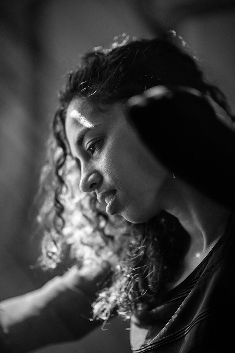Portrait en noir et blanc d'une jeune femme dans un bâtiment abandonné. La lumière éclaire son visage et se chevelure.