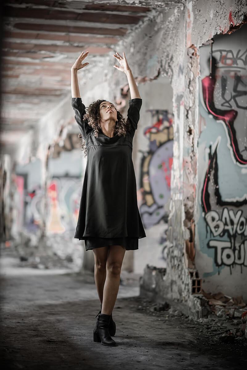 Portrait d'une jeune femme dansant dans un bâtiment abandonné, les bras levé au-dessus de sa tête.