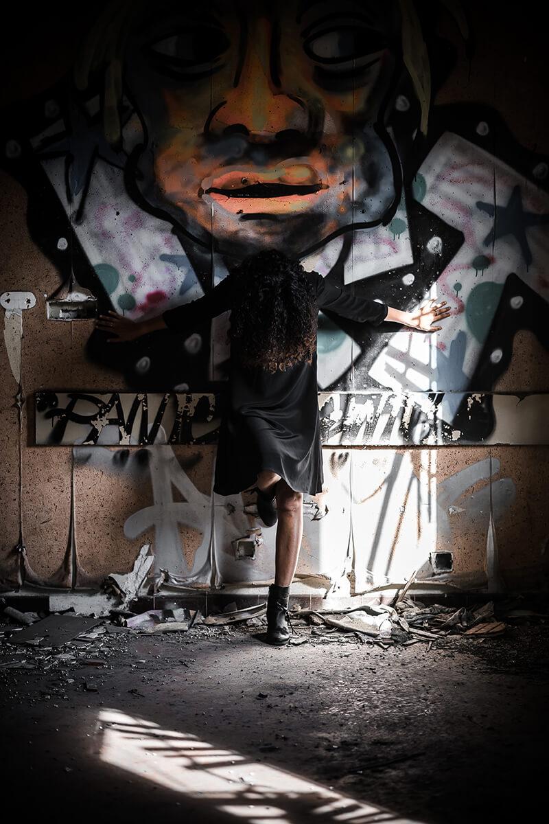 Portrait d'une jeune femme dans un bâtiment abandonné. La jeune femme est appuyée contre un mur, les bras en croix. Sa tête est courbée en avant.