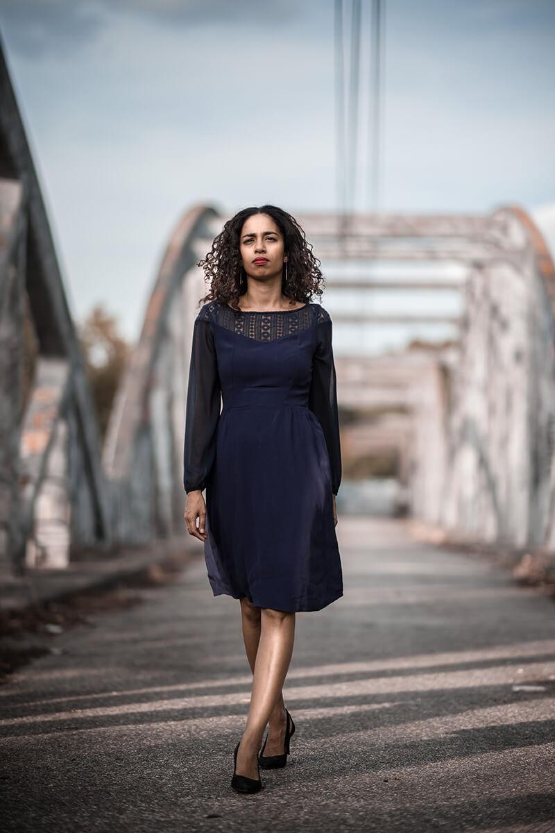 Portrait d'une jeune femme en robe bleue, marchant sur un pont désaffecté à Toulouse.